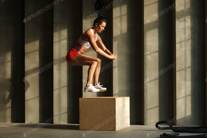 sportswoman jumps on crossfit box in gym