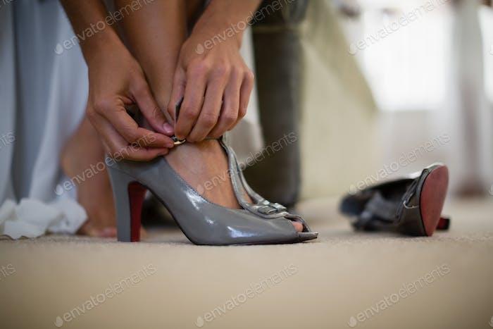 Bride wearing a wedding shoe