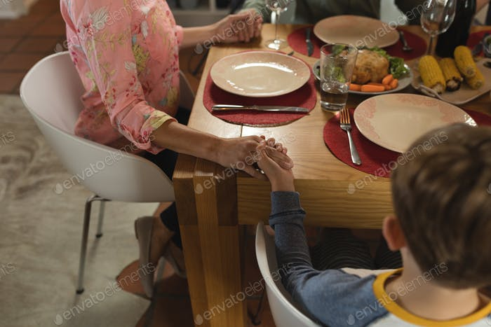 Close up of hands of family praying together before having meal on dining table at home