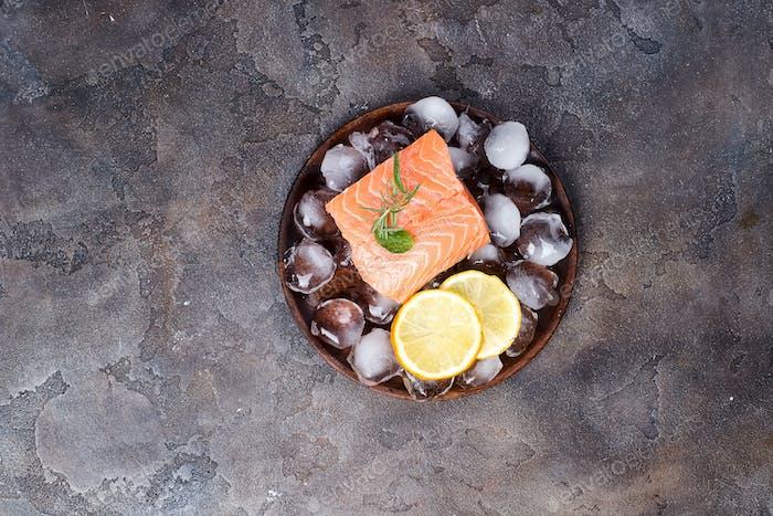 Filetes de salmón sobre Hielo con rodaja de limón sobre plato de De madera. Proteínas magras.