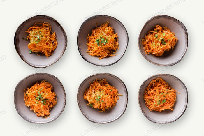Set of plates with russian korean salad on white isolated background