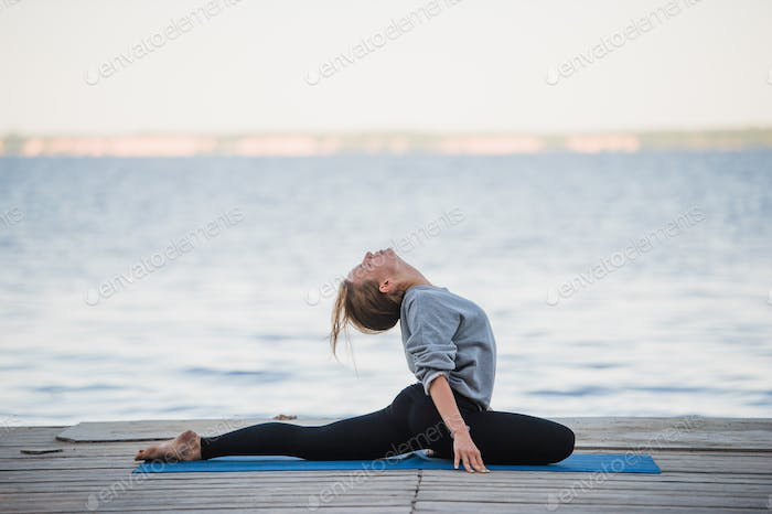 Pretty woman practicing yoga at a lake