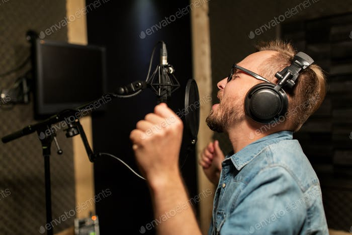 man with headphones singing at recording studio
