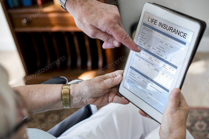 Senior couple reading life insurance form in tablet