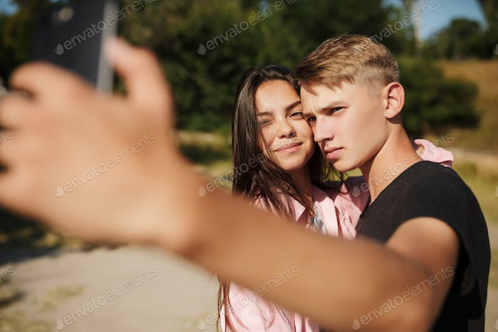 Young beautiful couple standing and making selfie in park