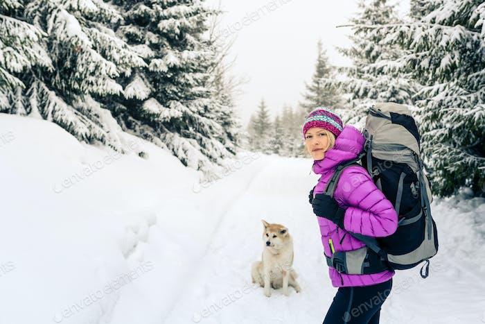 Glückliche Frau zu Fuß im Winterwald mit Hund