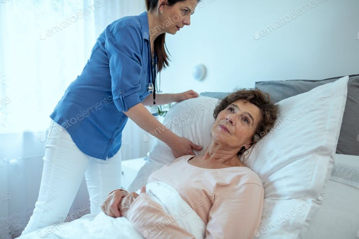 Home Caregiver Adjusting Pillow For Elderly Female Patient.