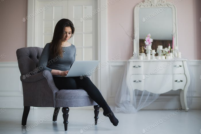 Young woman with laptop sitting on armchair at home