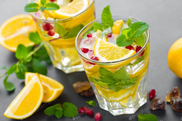 Lemon mojito cocktail with fresh mint and pomegranate, cold refreshing summer drink or beverage