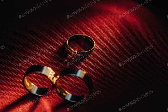 Two wedding rings and one engagement ring on a red background. three Gold rings of a couple in love
