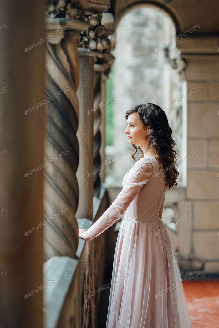 Ein Mädchen in einem hellrosa Kleid vor dem Hintergrund einer Medieva Burg