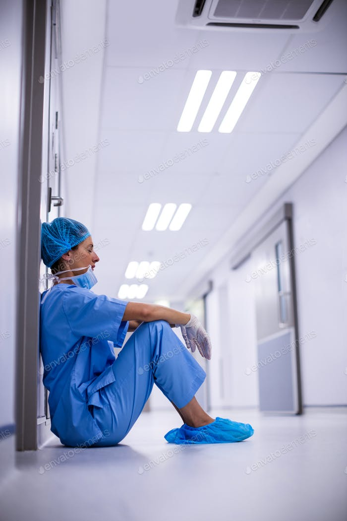 Sad surgeon sitting on floor in corridor