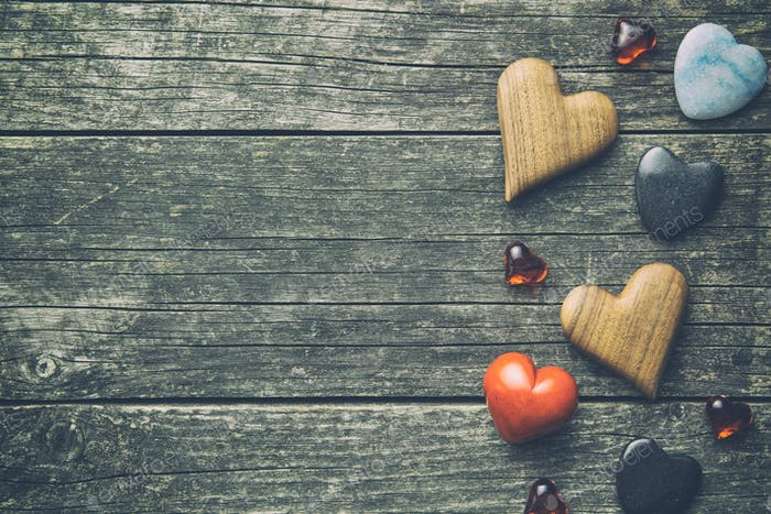 Various hearts on wooden table.