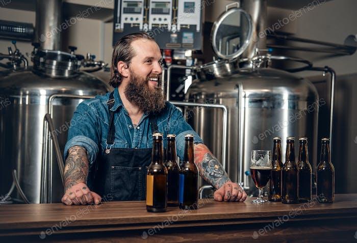Ein Mann, der Bier in der Mikrobrauerei präsentiert.