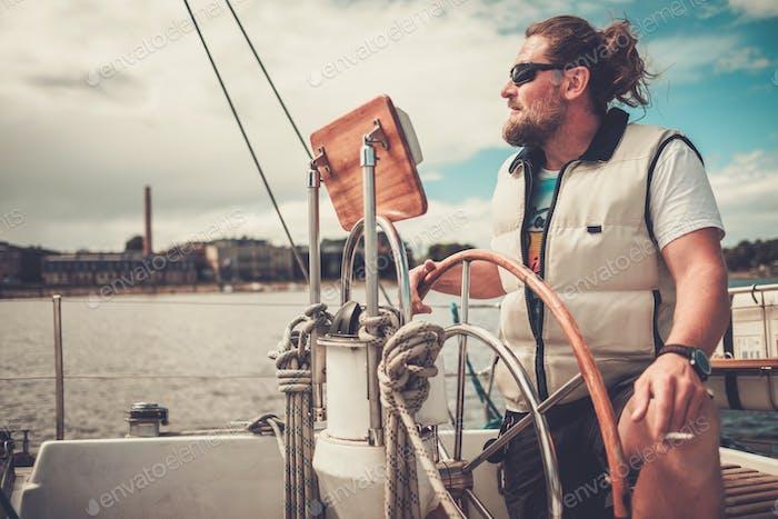 Capitán en un yate detrás del volante
