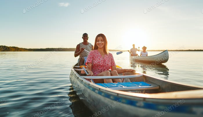 Young friends canoeing on a lake in the late afternoon