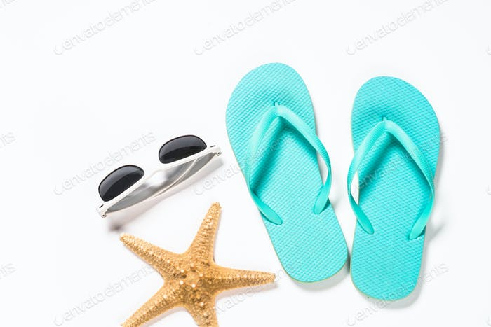 Blue flip flops, sunglasses and starfish on white background