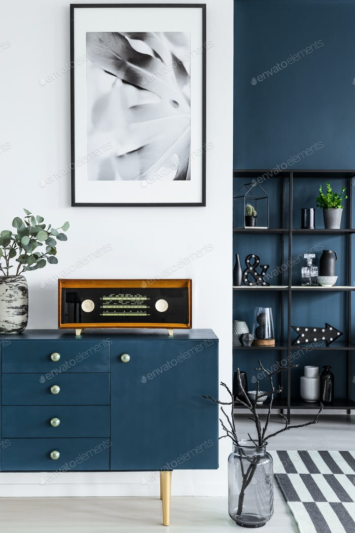 Close-up of a painting, blue cabinet, retro radio and glass vase