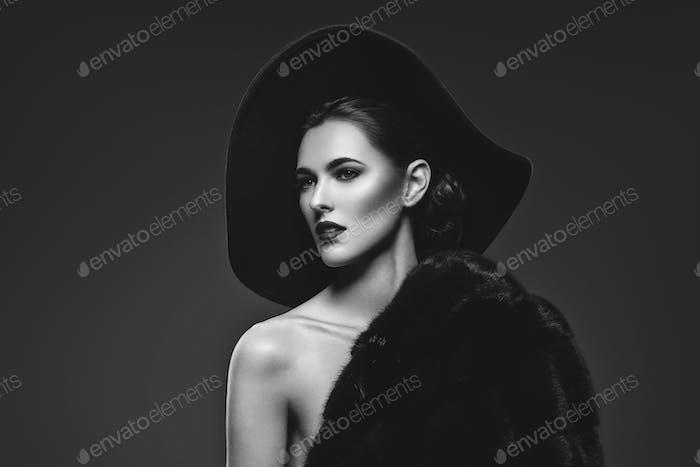 Schöne Mädchen in Pelzmantel und Hut