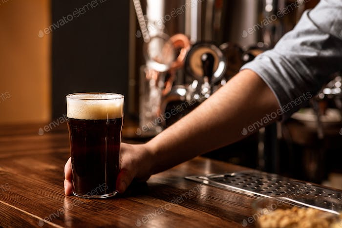 Fresh dark beer with foam in pub. Bartender gives glass to dark drink with foam on bar counter
