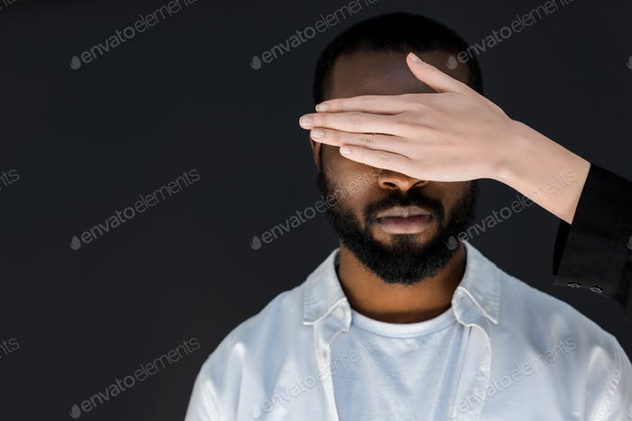 Imagen recortada de novia cerrando ojos de novio afroamericano aislado en negro