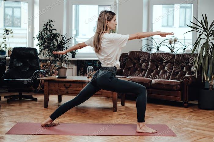 Flexible chica esporive posando en postura de yoga con las manos extendidas en la sala de estar