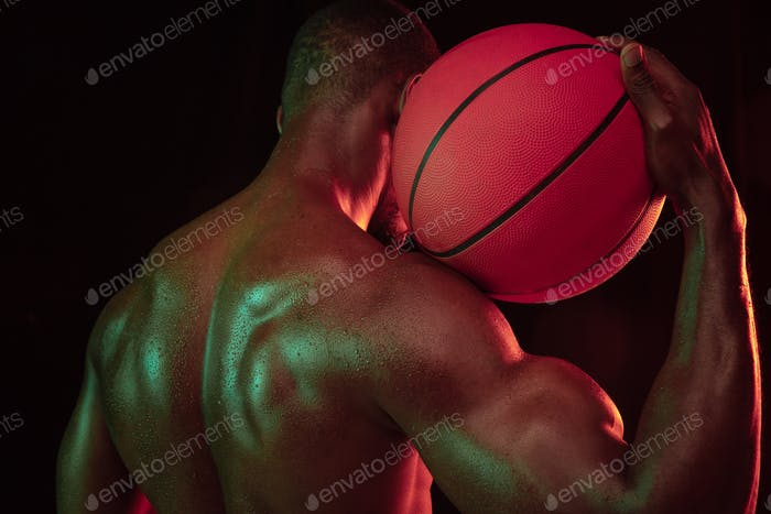 Young african-american basketball player against dark background