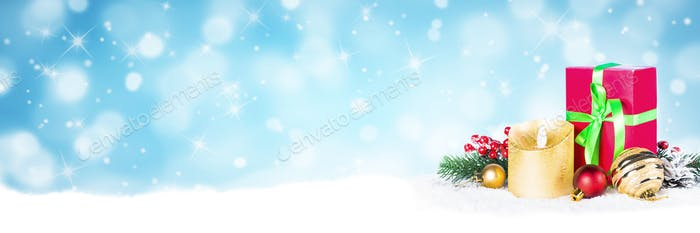 Red and golden decorations in snow on blue blurred background