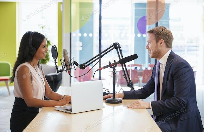 Mujer joven entrevistando a un invitado en un Estudio para un podcast