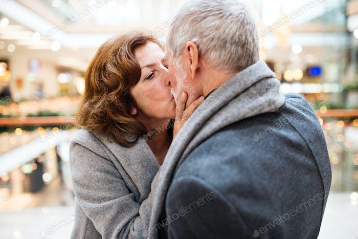 Senior couple doing Christmas shopping, kissing.