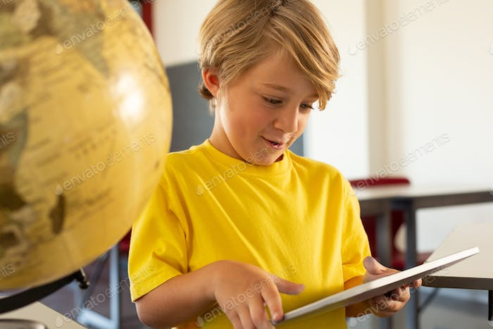 Front view of a Caucasian boy using digital tablet in a classroom at elementary school