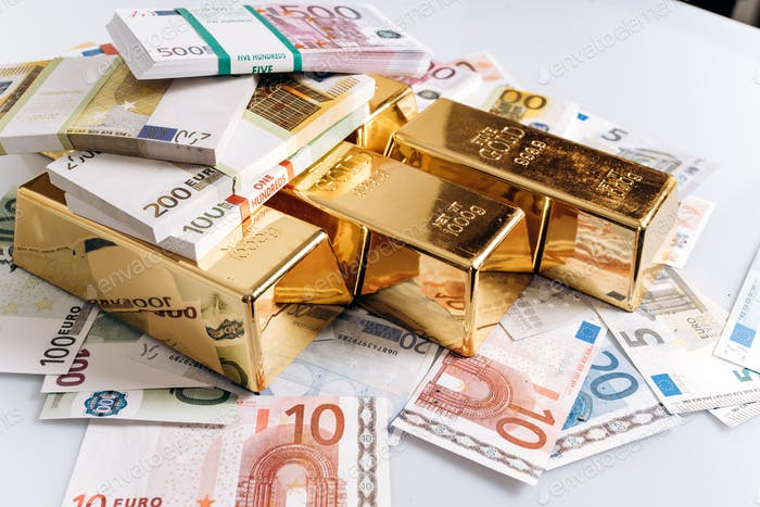 Gold bullions at euro banknotes closeup background. Gold bars lie on Euro banknotes