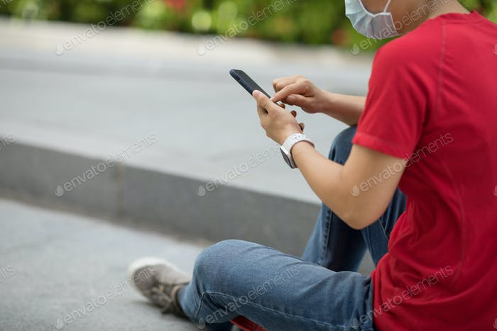 Asian woman sit on skateboard using smartphone in modern city