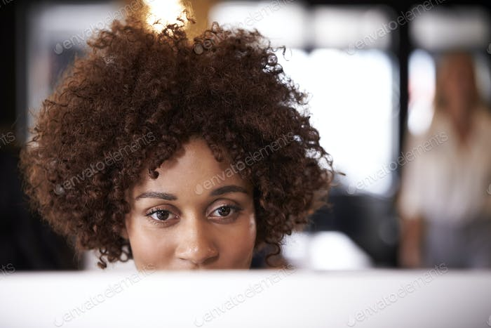 Close up of millennial black female creative using computer at a desk in an office, head shot