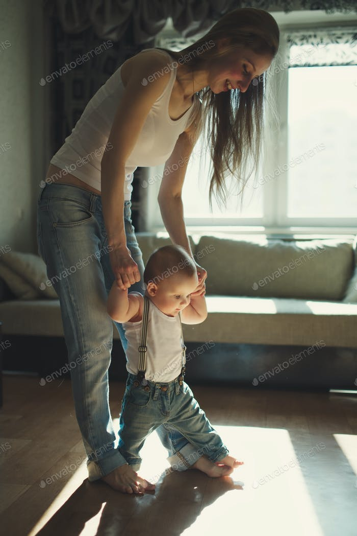 beautiful mother teaches baby to walk