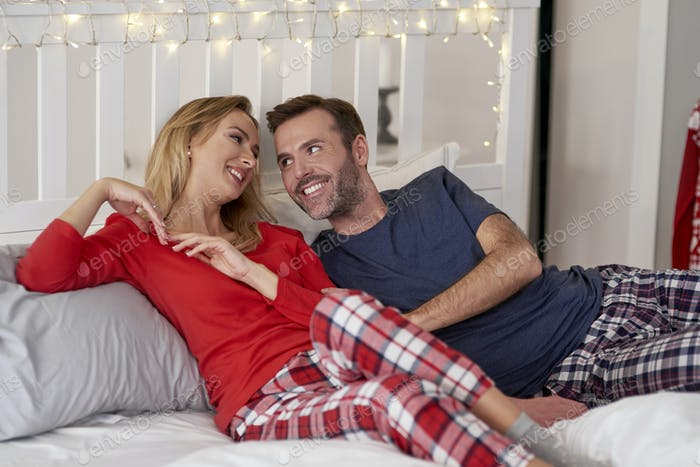 Loving couple flirting in bed