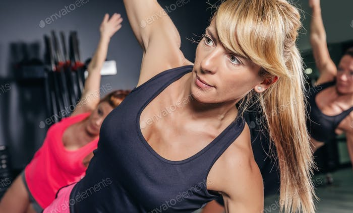 Woman doing exercises in aerobic class with a group