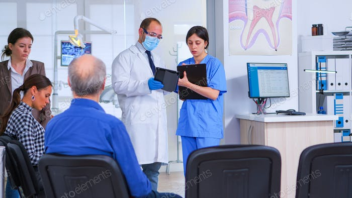 Dental specialist speaking with assistant standing in waiting room