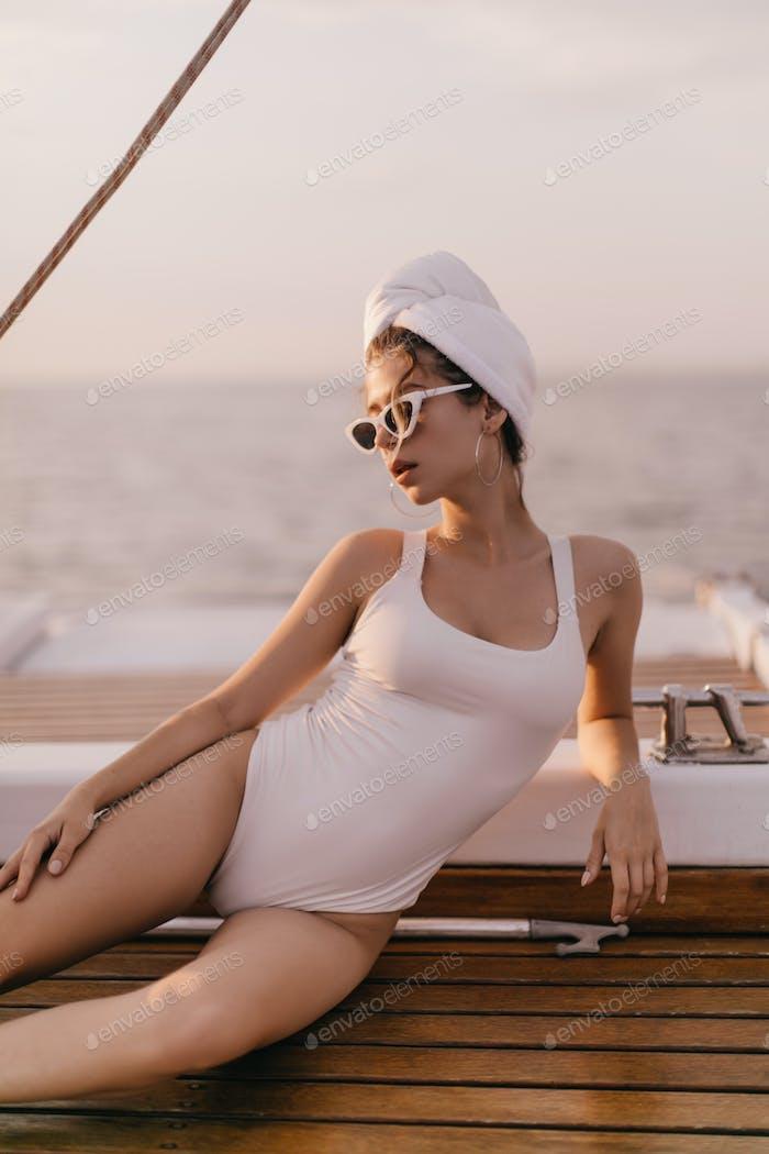 Lifestyle-Porträt einer hübschen jungen Dame mit brüniertem Körper im weißen Badeanzug, stylischer Sonnenbrille und