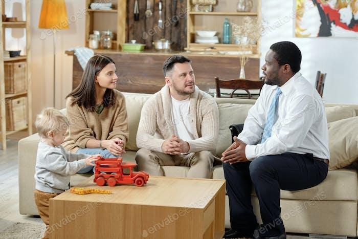 Mann berät Familie auf Immobilien Hypothek