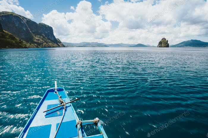 Island hopping Tour boat hover over blue ocean between exotic islands on excursion trip exploring