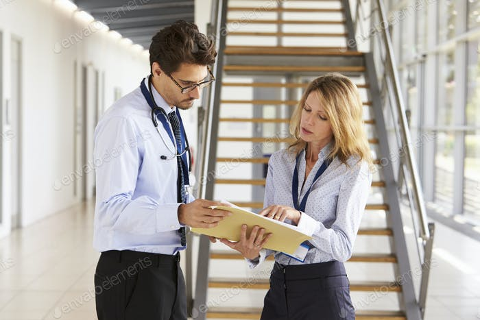 Young male and female doctors discuss notes at meeting