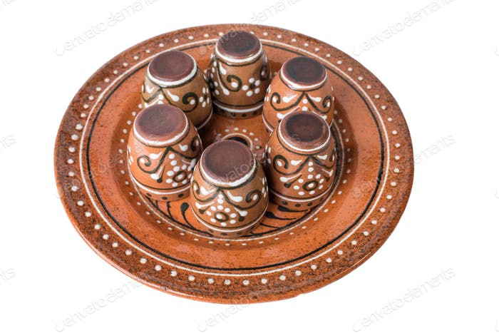Ceramic plate with set of varnished cups.