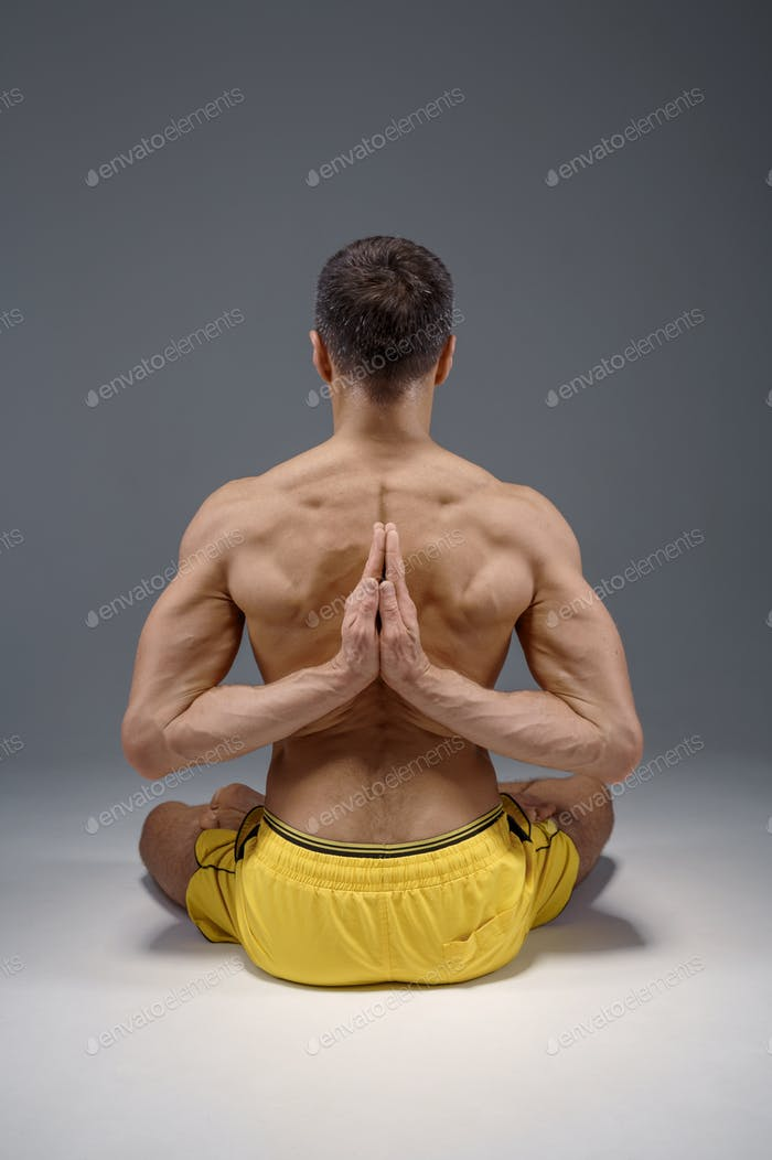 Yoga sits with hands behind his back
