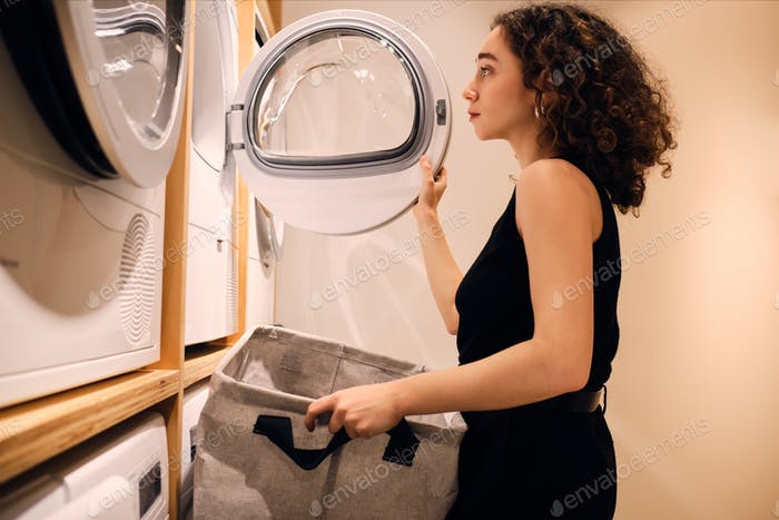 Vista lateral de la hermosa chica cargando ropa en lavadora en lavandería de autoservicio
