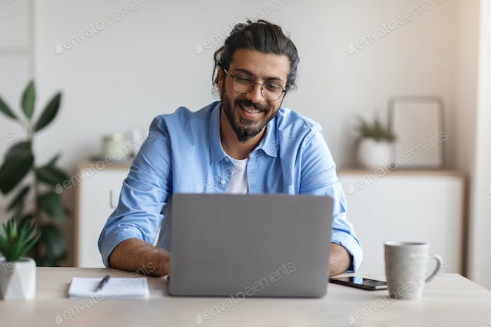 Freelance Work. Happy Millennial Indian Man Working On Computer At Home Office