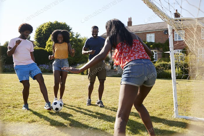 Black adult friends having a fun game of football in garden