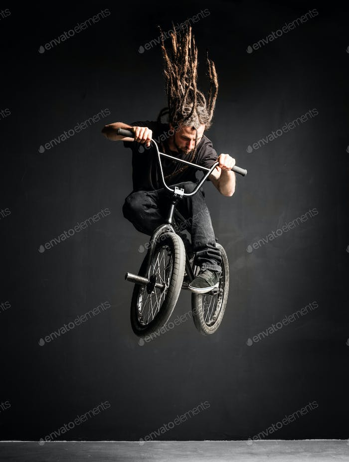 Young man with dreadlocks jumping on his BMX bike.