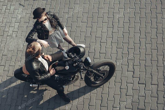 jóvenes pareja sentado en la Vintage Moto