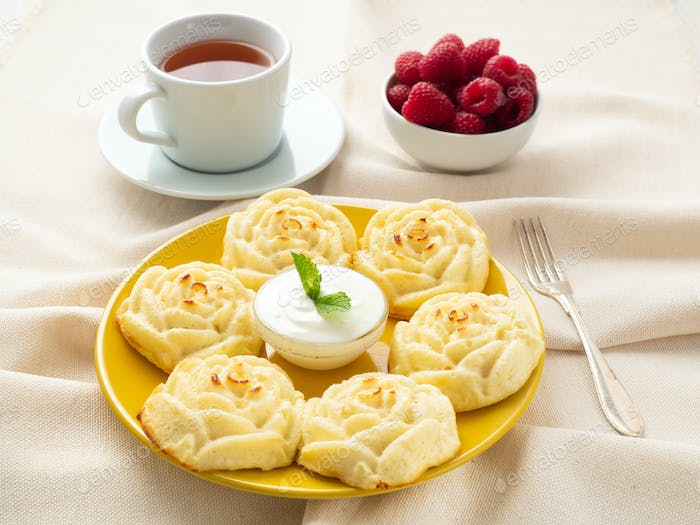 Diet cheese pancakes, rose shape, on yellow plate with tea, raspberry on textile linen napkin